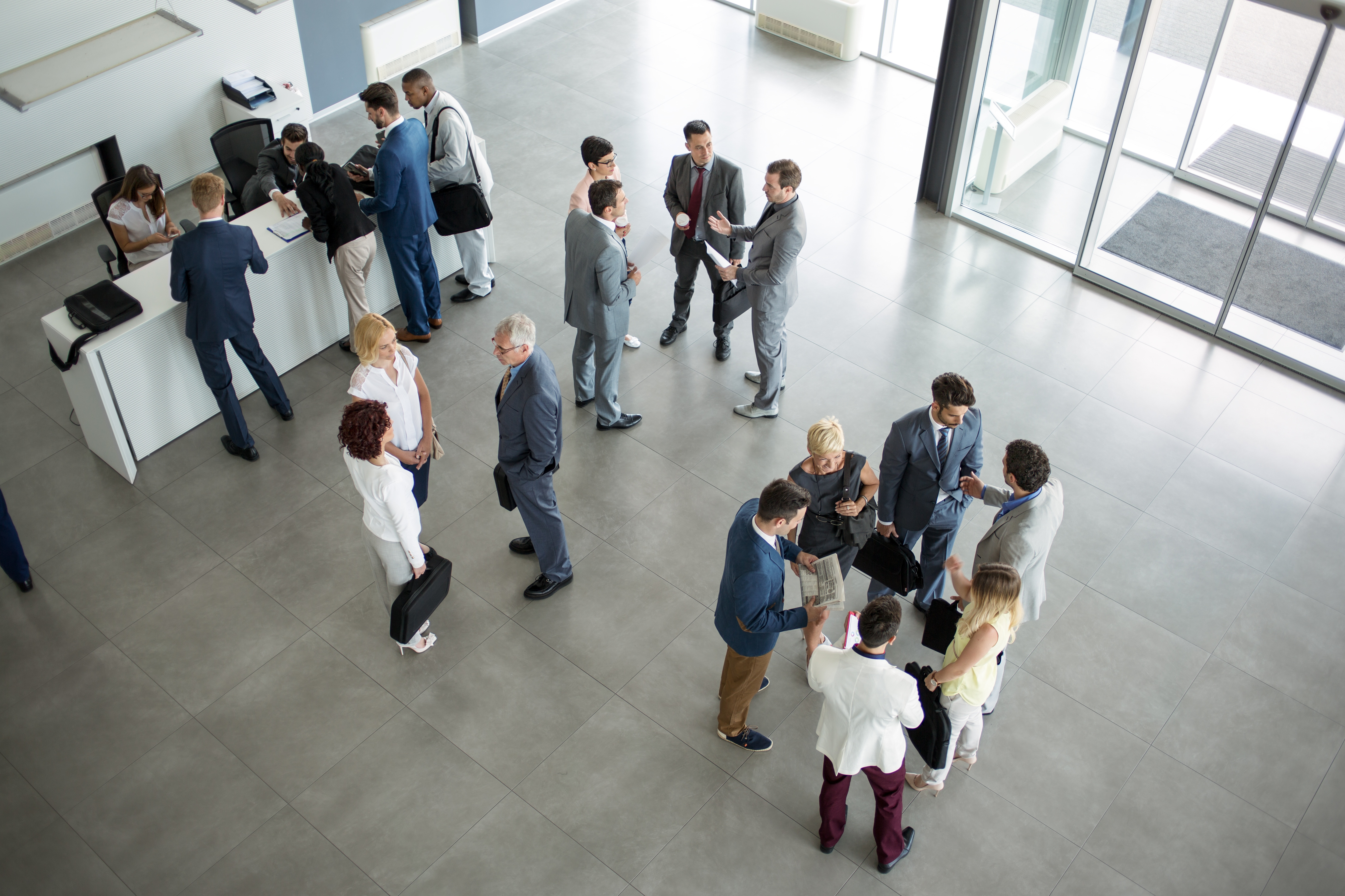 People in the lobby of an office building waiting to go to a Doherty IT event