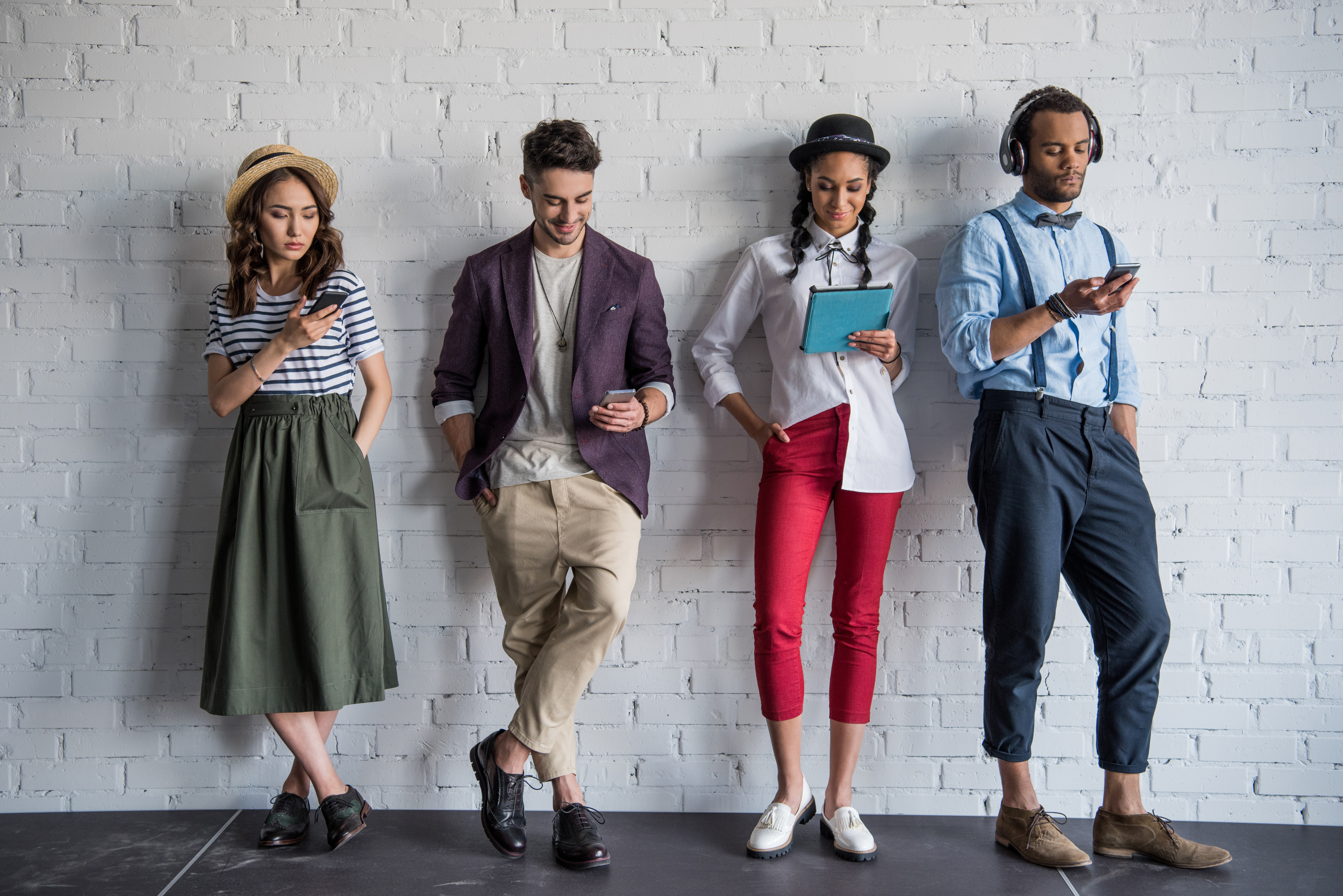four millennials working on their portable devices - working practices