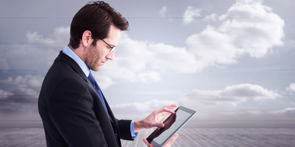 Businessman standing while using a tablet pc against clouds in a room.jpeg